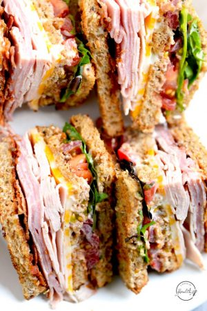 Club sandwich closeup with turkey, ham, bacon, colby jack cheese, lettuce tomato and bacon
