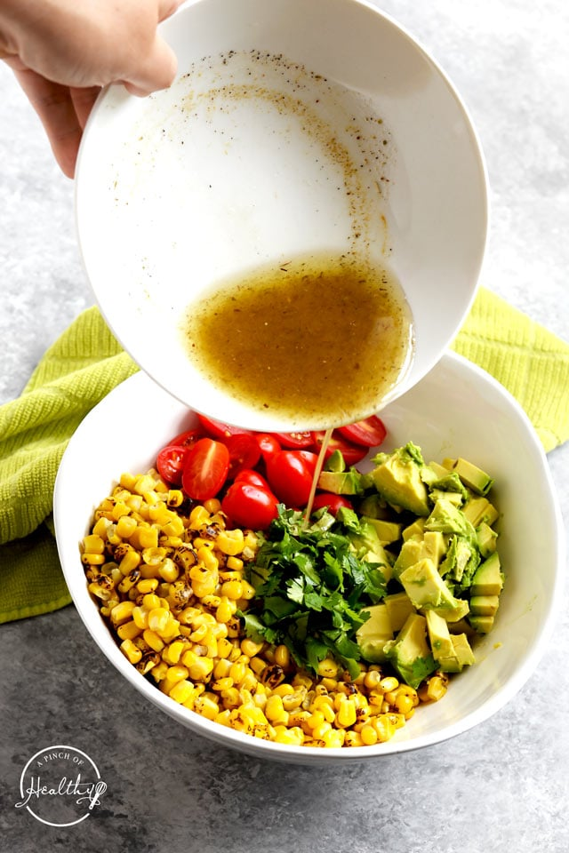 pouring dressing on corn salad with avocado tomato and cilantro