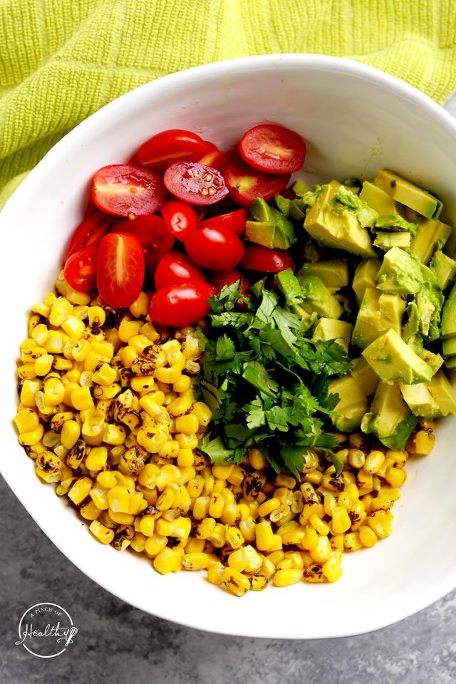 Making corn salad with avocado tomato and cilantro