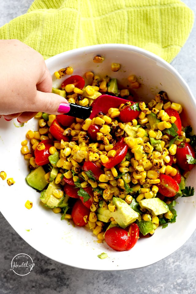 stirring corn salad in a white bowl