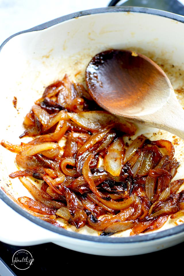 Caramelized onion in a white pan with wooden spoon