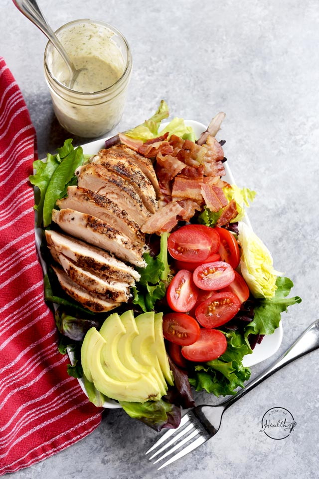 Chicken BLT salad overhead on a white plate with a jar of ranch dressing