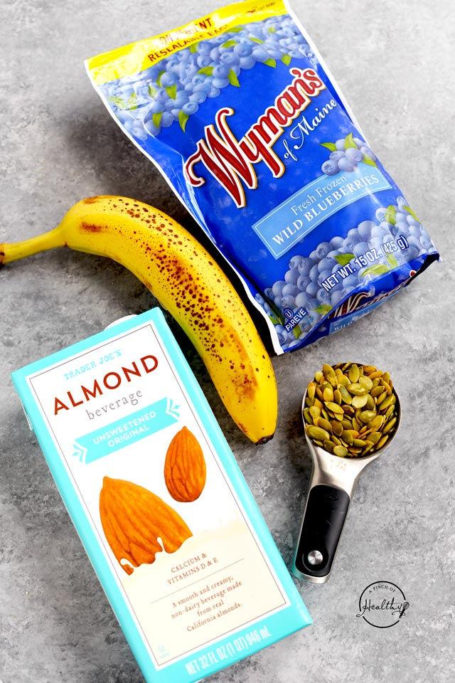 Banana almond milk blueberries and pumpkin seeds on a gray background