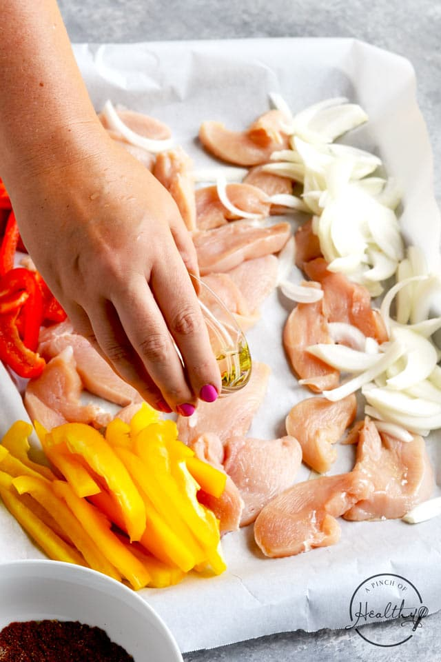 Drizzling oil on chicken and vegetables for sheet pan easy chicken fajitas