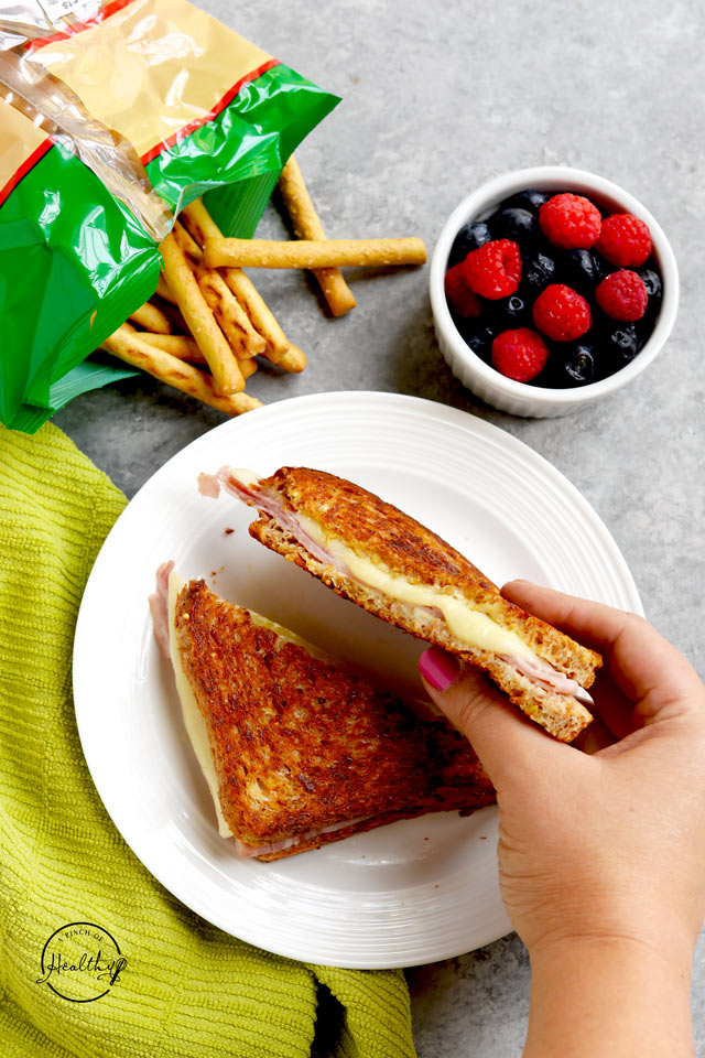 Grilled ham and cheese sandwich with berries and pretzel sticks