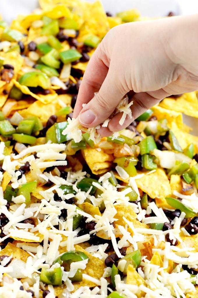 sprinkling cheese on vegetarian nachos
