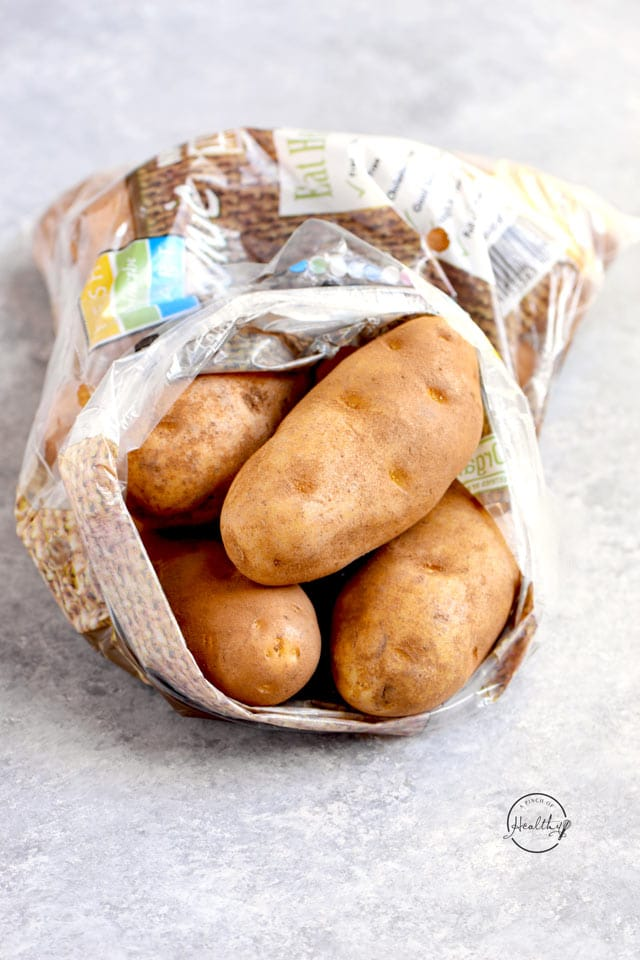 Russet potatoes in a bag on gray counter