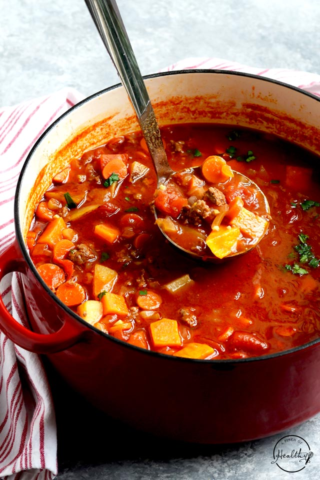 Hamburger soup in a red pot with a ladle scooping it out