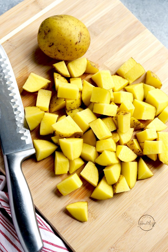 Yukon gold potatoes, diced on a wood cutting board with a knife