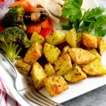 air fryer roasted potatoes on a white plate with chicken and veggies