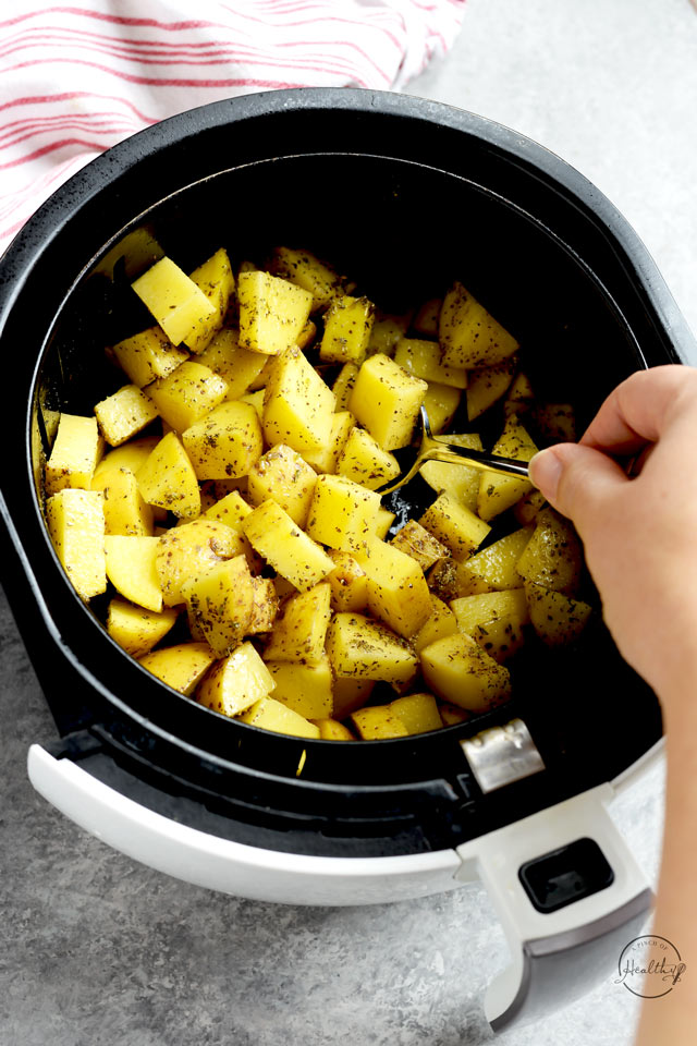 tossing potatoes with herbs and garlic with a spoon in the air fryer basket