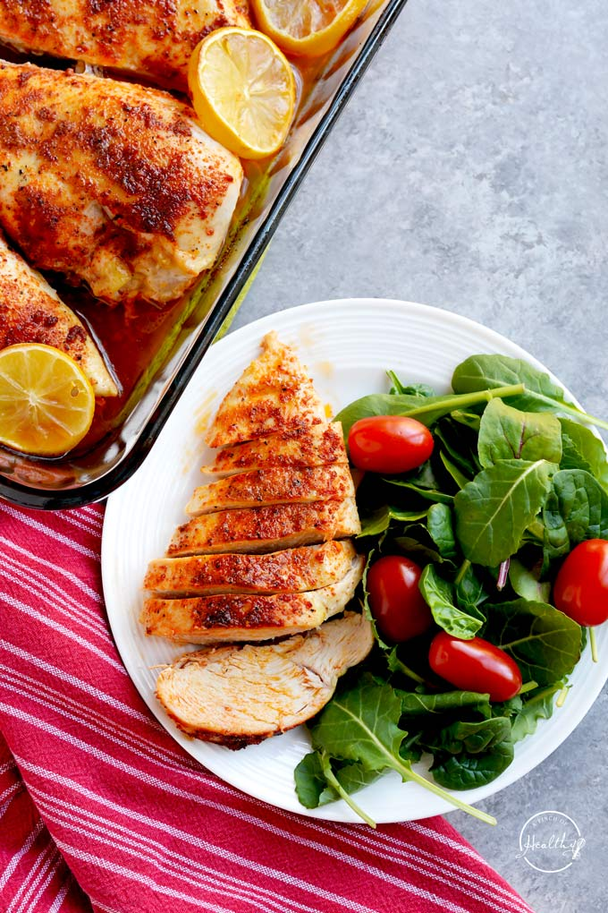 Baked chicken breast on a white plate with a side salad next to a red towel and a pan of more baked chicken breasts