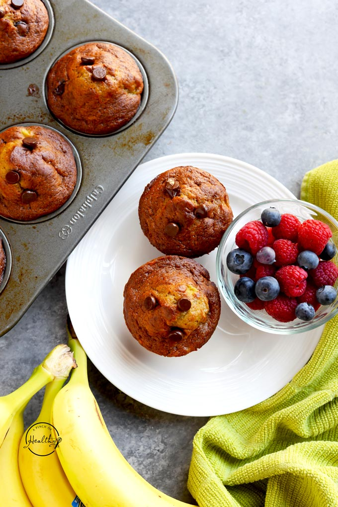 Banana chocolate chip muffins on a white plate with berries on a gray background