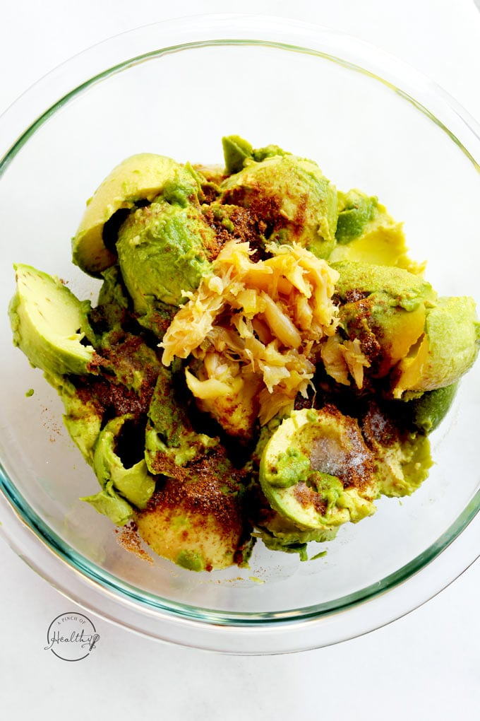 avocados with cumin, salt, lime juice and roasted garlic in a clear bowl on white surface