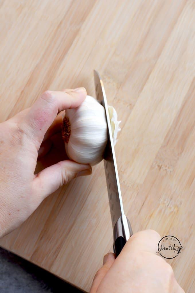 Cutting top of garlic bulb on wooden cutting board