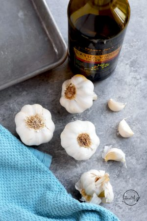 Garlic bulbs, plus a few cloves on a gray background with bottle of olive, baking sheet and blue towel