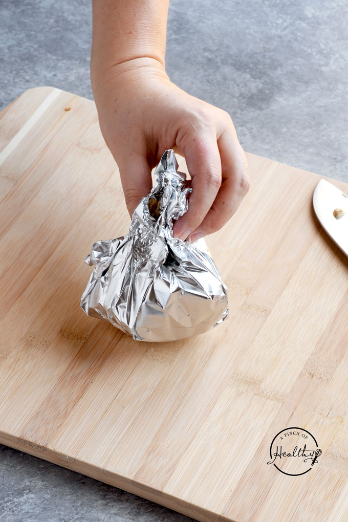 How to roast garlic in foil wrapping the garlic in aluminum foil