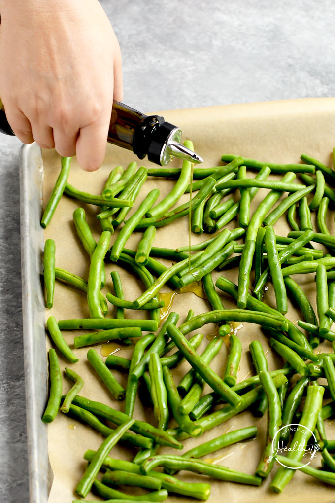drizzling olive oil on green beans on a baking sheet