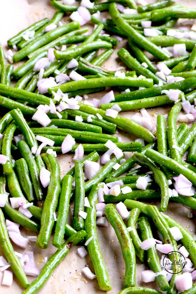 raw green beans with shallot on baking sheet