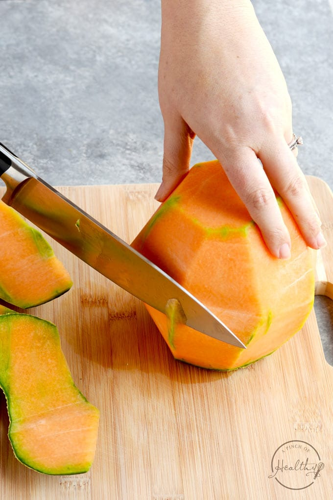 peeling a melon with a sharp knife on wood cutting board