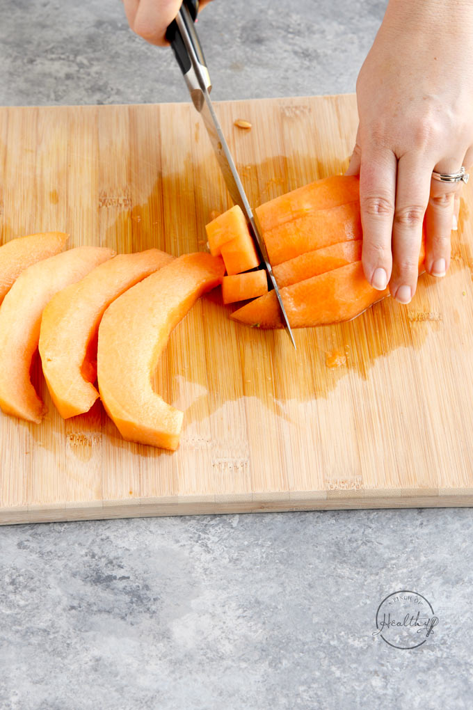 cutting a cantaloupe into cubes on a wood cutting board