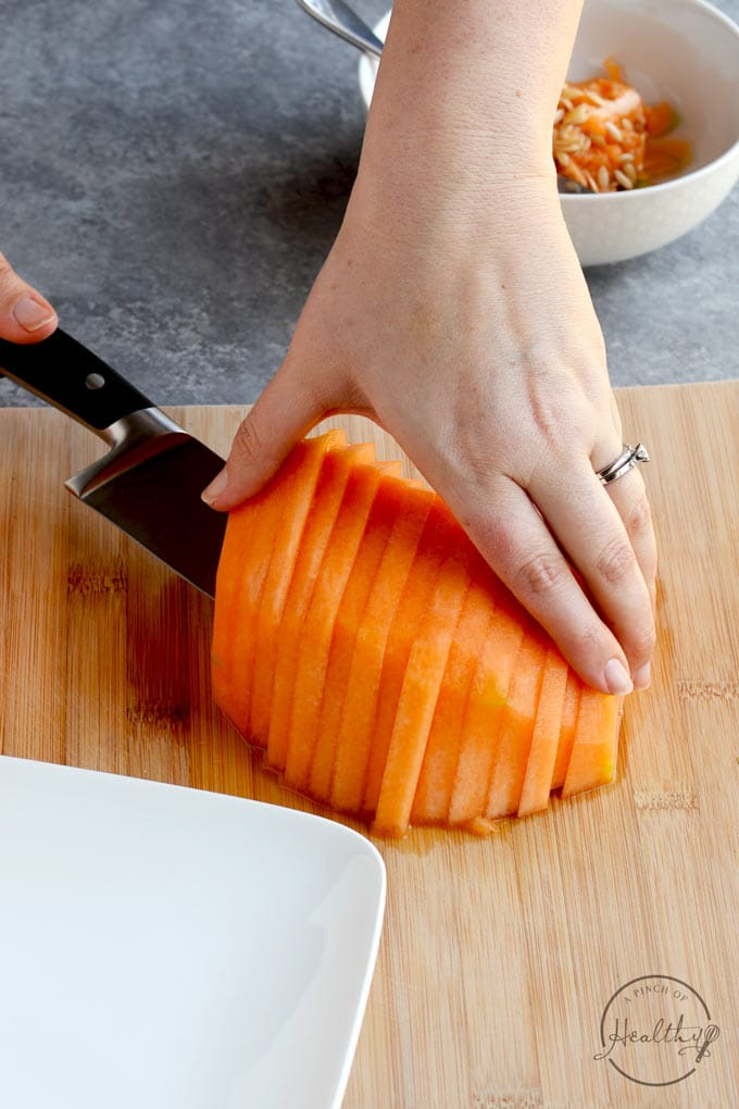 scooping thin cantaloupe slices up with a knife
