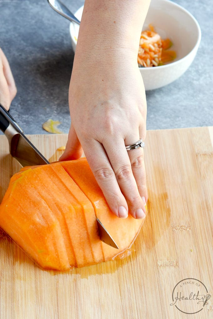 cutting cantaloupe into thin slices on a wood cutting board