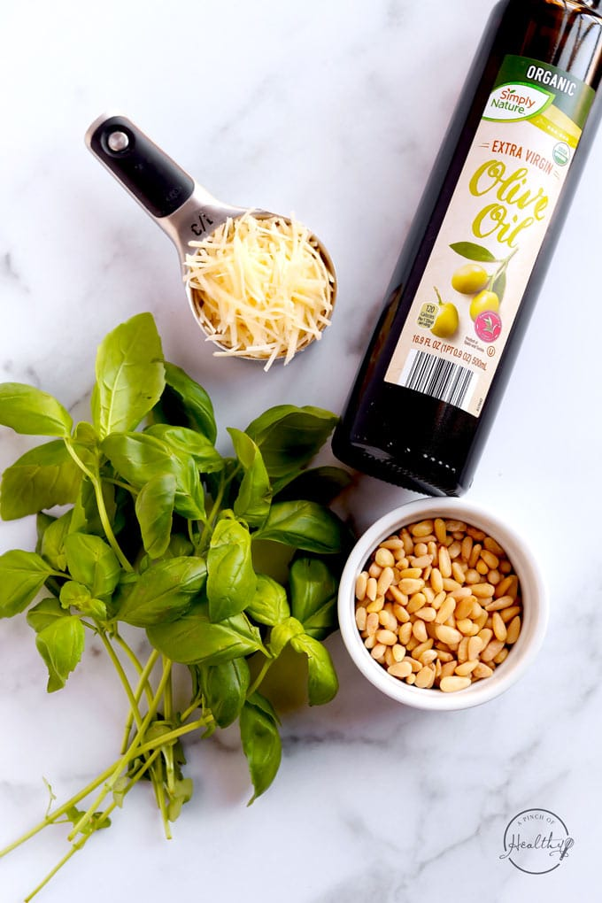 pesto ingredients parmesan pine nuts olive oil and basil on a marble surface