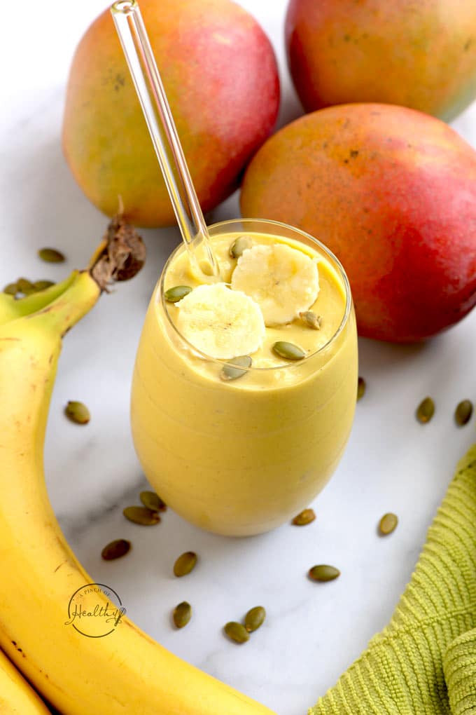 mango smoothie with bananas and pumpkin seeds on a white surface with green towel