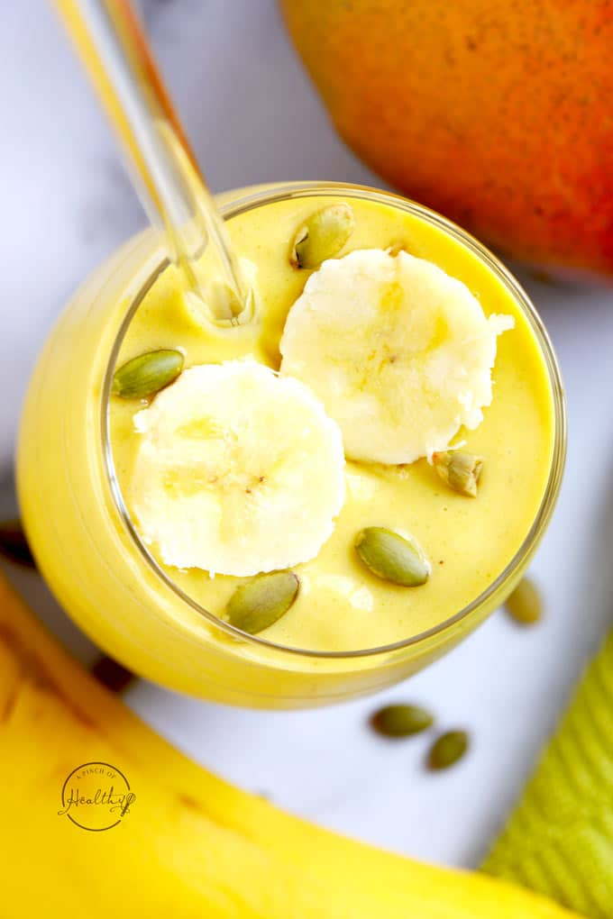 mango smoothie from overhead with sliced bananas and pumpkin seeds