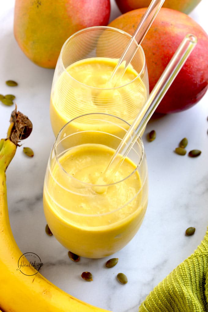 mango smoothie in two glasses with glass straws