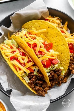 Ground beef tacos in a bowl with white paper liner