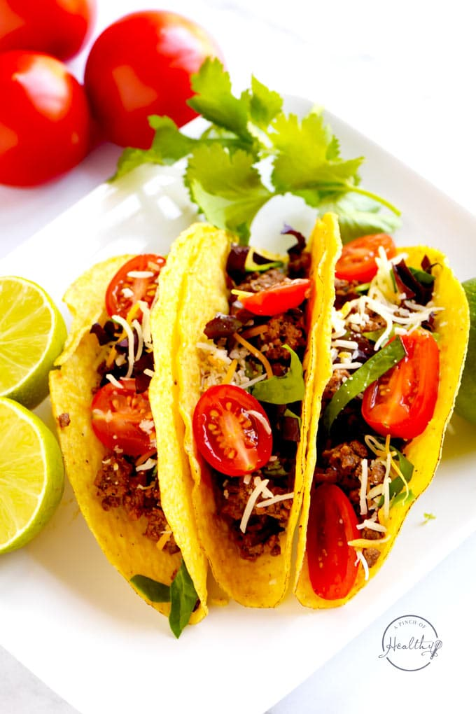 closeup of three ground beef tacos on a white plate