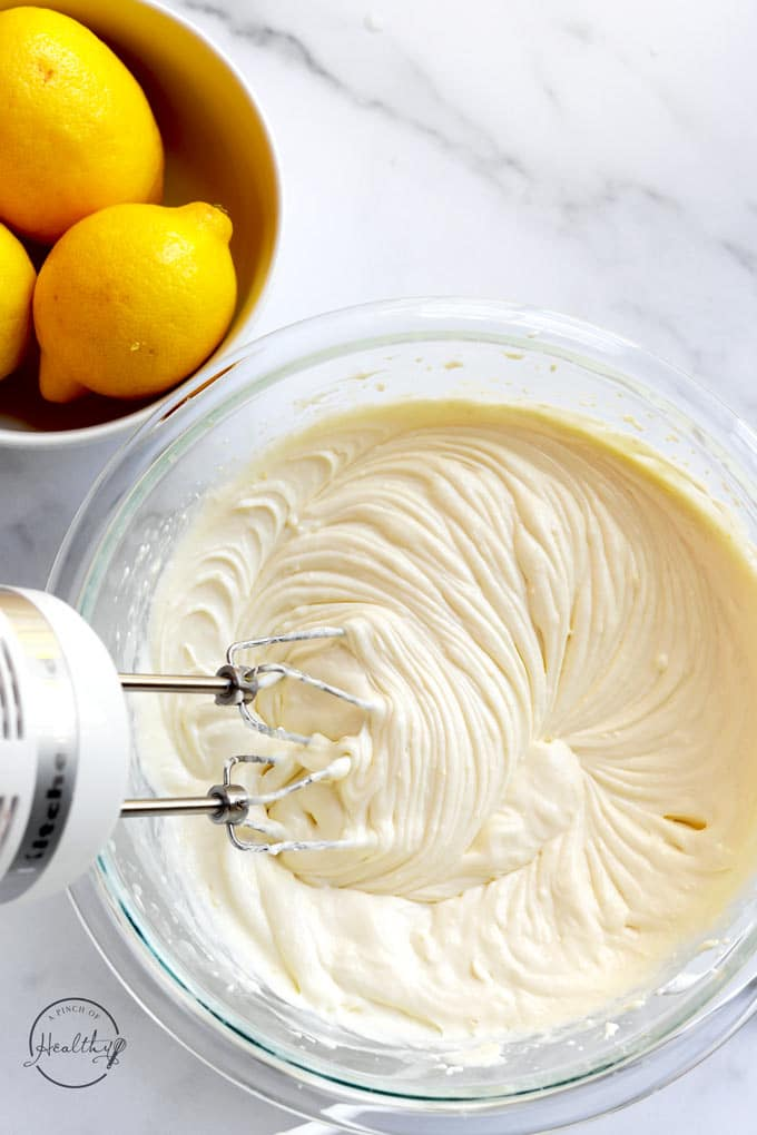 Mixing together lemon cheesecake filling in a clear bowl until creamy