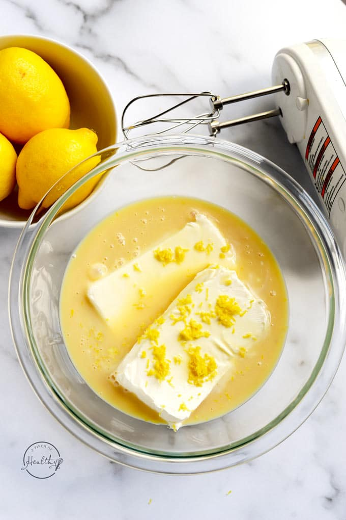 Ingredients in a clear bowl to make no bake lemon cheesecake
