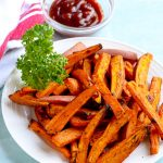 Air fryer sweet potato fries on a white plate with parsley