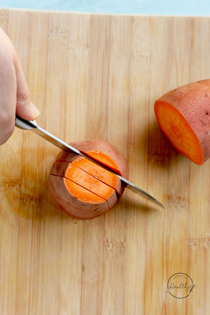 cutting sweet potatoes on a wood cutting board