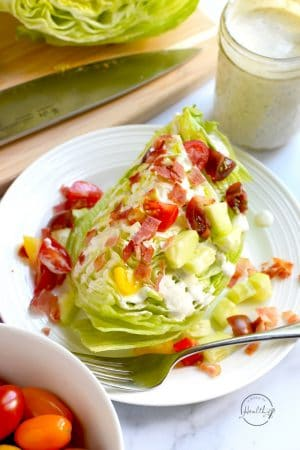 closeup wedge salad with tomato, bacon, cucumber and ranch