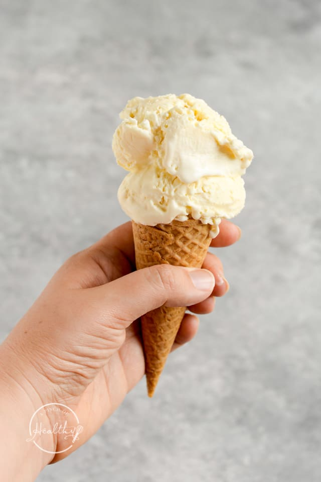 hand holding vanilla ice cream in a cone over gray background