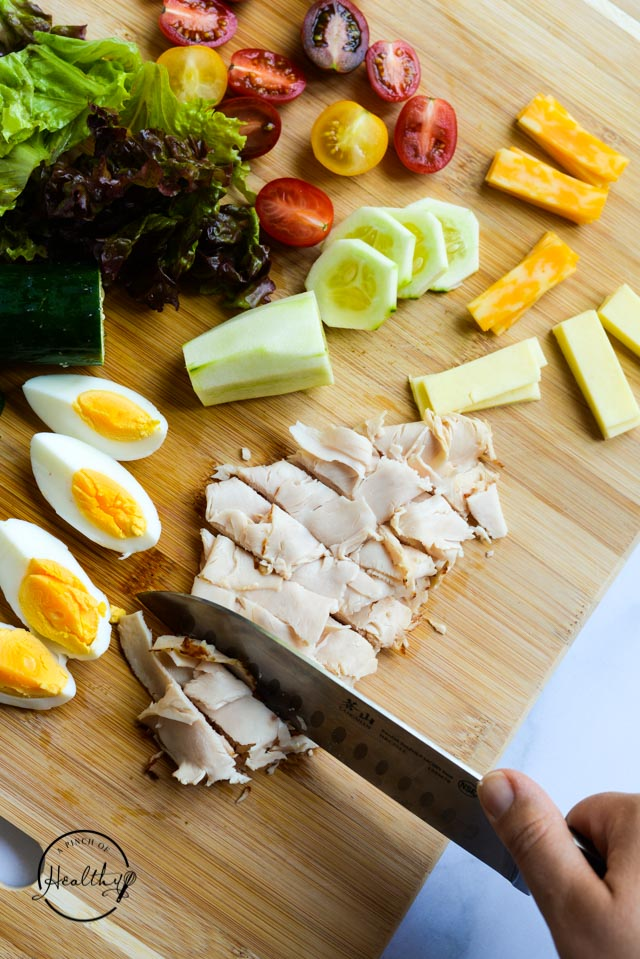 chopping deli turkey on a cutting board with eggs, cucumber, cheese, tomato and lettuce