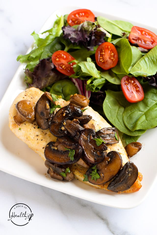 Chicken breast topped with mushrooms alongside green salad on white plate