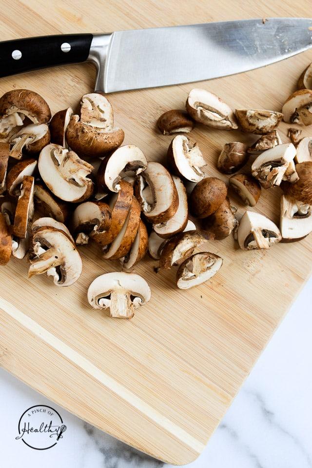 baby portabella mushrooms sliced on a cutting board
