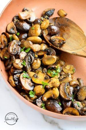 closeup sautéed mushroom in a copper pan