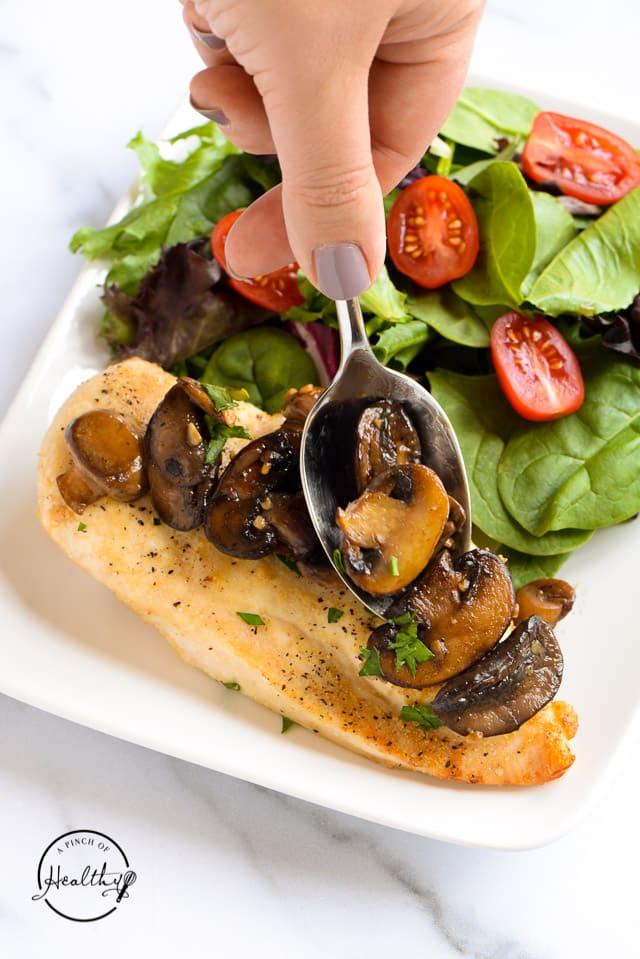 spooning sautéed mushrooms onto cooked chicken breast