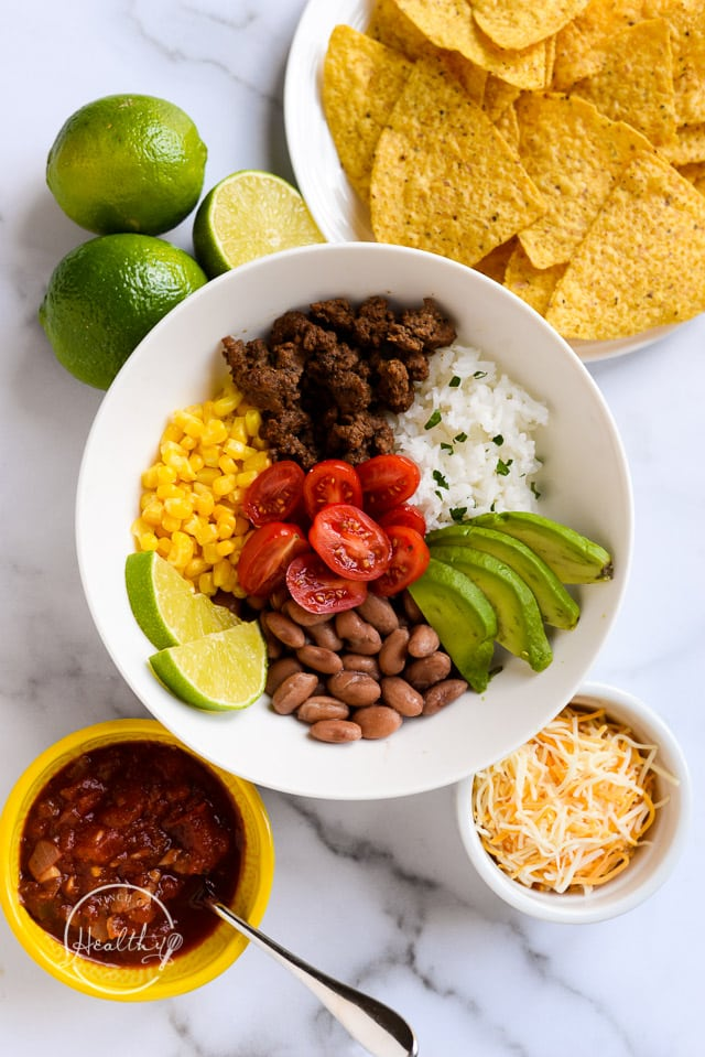 Taco bowl with ground beef, rice, corn, pinto beans, tomato, avocado and lime