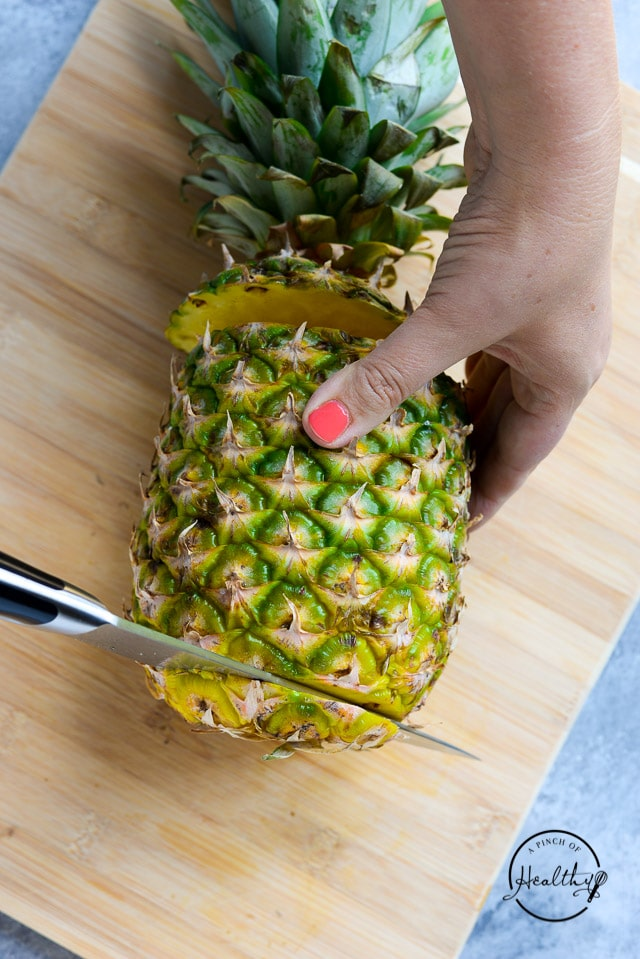cutting ends off pineapple on wood cutting board