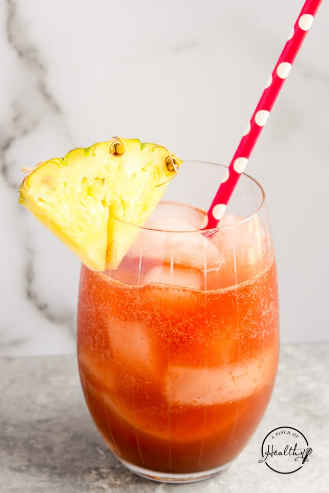 cocktail garnished with pineapple and red decorative straw