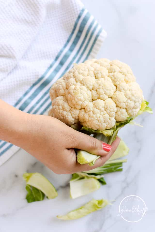 removing stems and leaves off a head of cauliflower