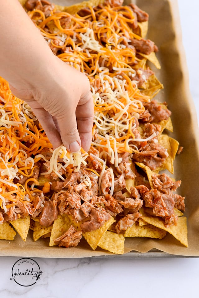 sprinkling cheese on tortilla chips to make chicken nachos