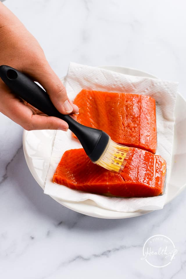 brushing olive oil on salmon filets